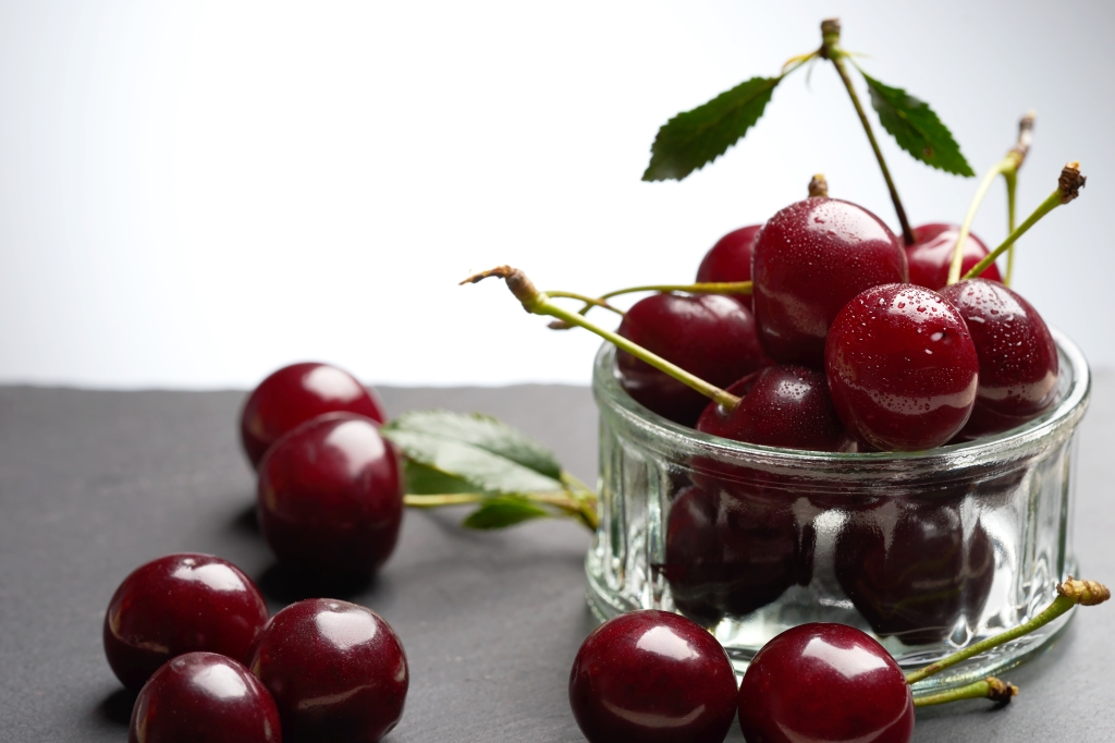 Food photography of cherries in a glass bowl